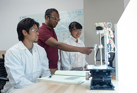 CSU Stanislaus student Will Cheung, left, and UC Merced graduate student Melissa Xu, right, continue the diagnostic project with Subramaniam, center.