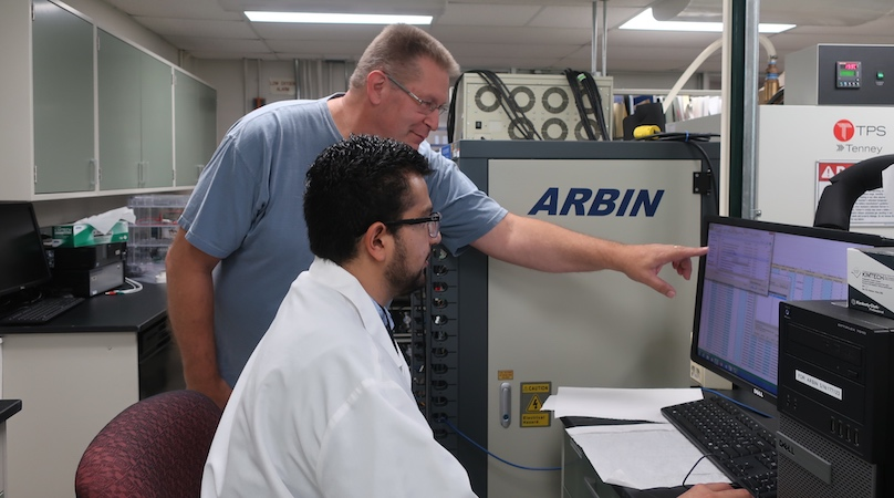 A student sitting at a computer with a NASA scientist standing behind him are working together in a laboratory.