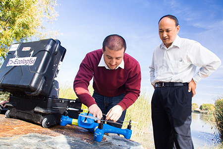 professor Chen, right, and student Brendan Smith work with drones.